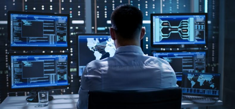 CyberSecurity - System Security Specialist Working at System Control Center Room - image courtesy of Depositphotos.