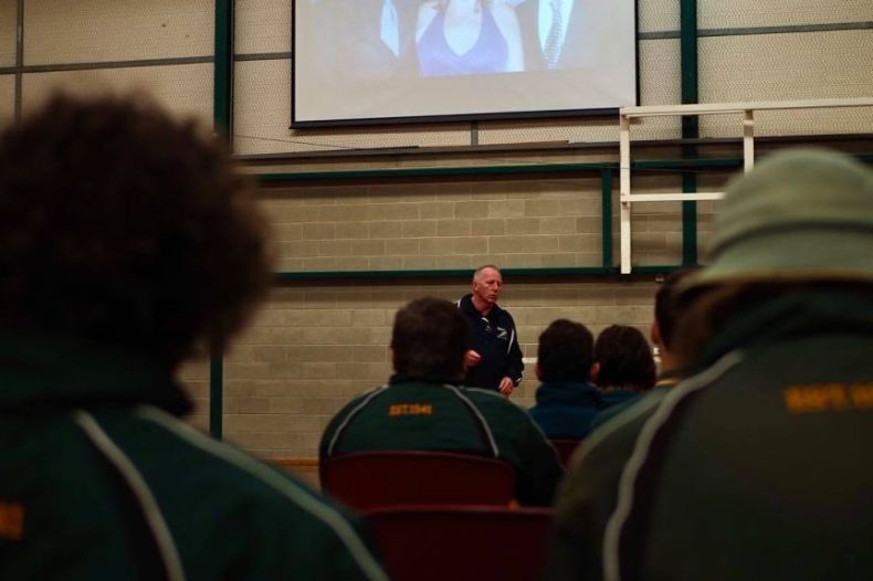 Male school students sit before Neil Davis, who stands in front of the crowd beneath a large projected image of his family.